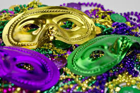 Mardi Gras masks and beads in traditional colors of green, gold and purple.
